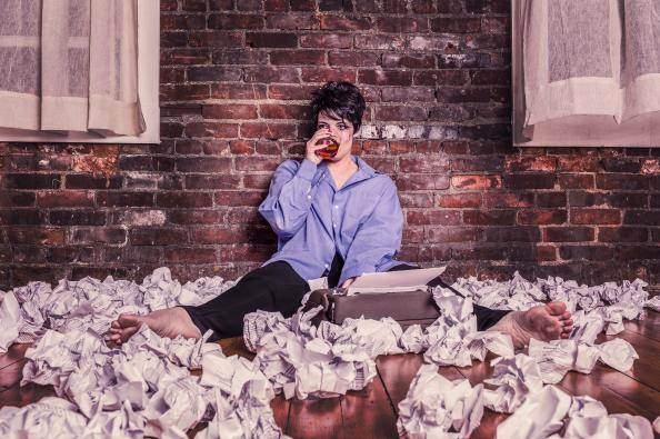 gratisography girl writer surrounded by crumpled up pages and typewriter deadline