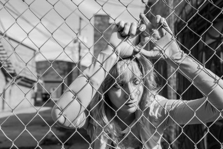 gratisography leaning against fence giving up